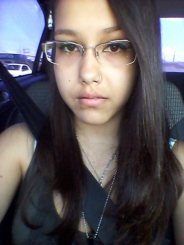 Girl with long hair and glasses driving