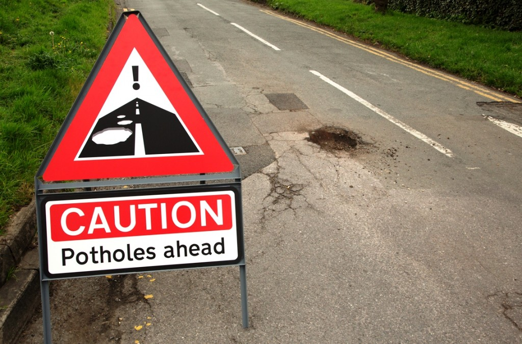 Potholes warning sign and road with pothole