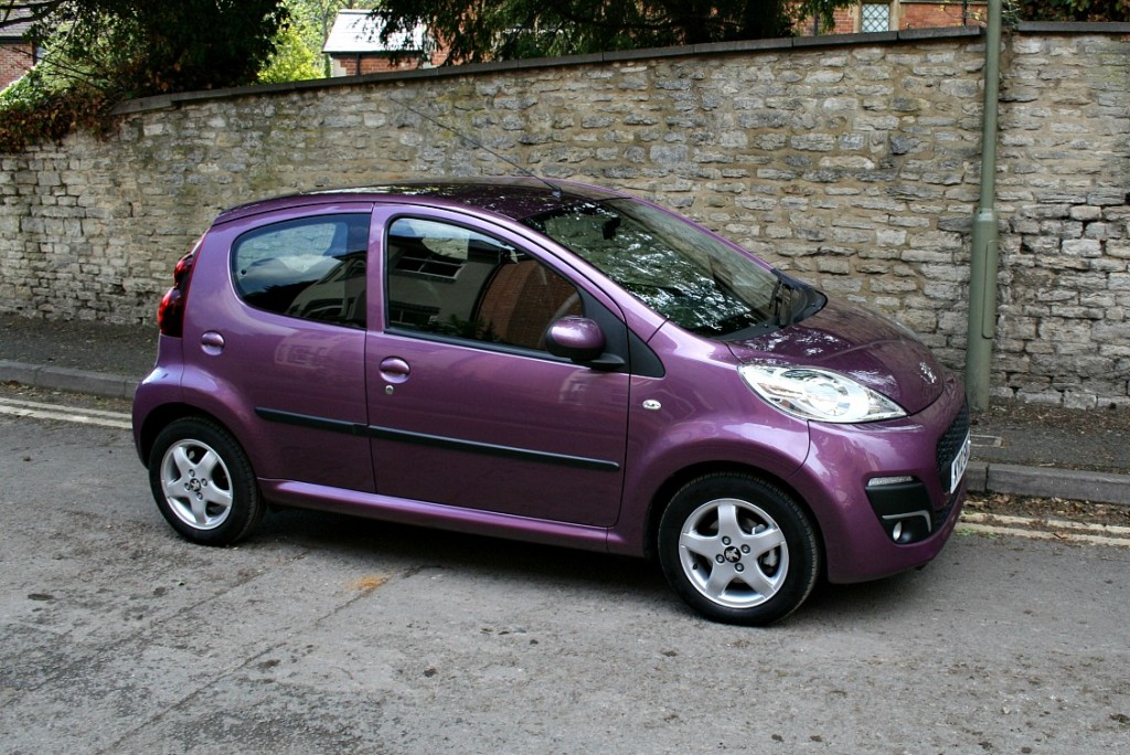 small aubergine-coloured car by a brick wall, side view