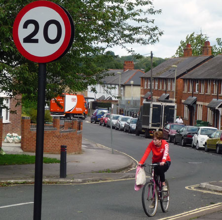 20 miles per hour road sign with cyclist in small town road