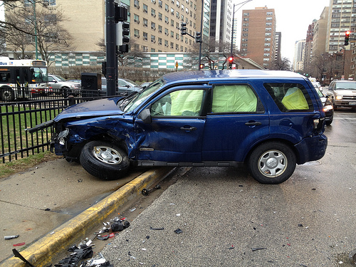 Accident - Blue SUV with destroyed front end against black railings